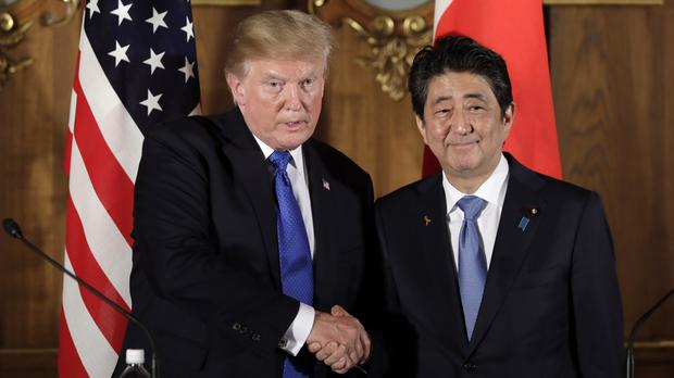Donald Trump shakes hands with Shinzo Abe during a joint news conference at the Akasaka Palace in Tokyo (AP)