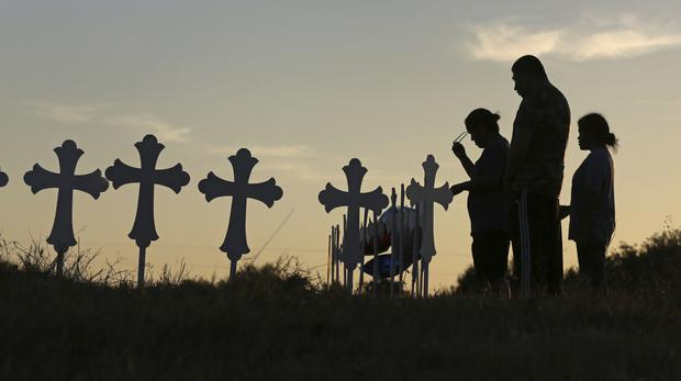 Prayers are said in front of some of the crosses placed in a field in Sutherland Springs, Texas (AP)