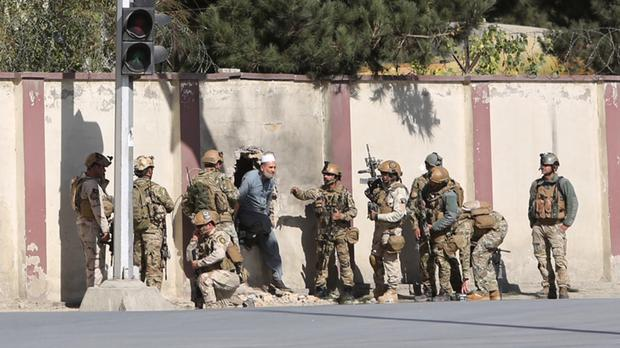 Afghan security personnel rescue a man from the Shamshad TV building (AP)