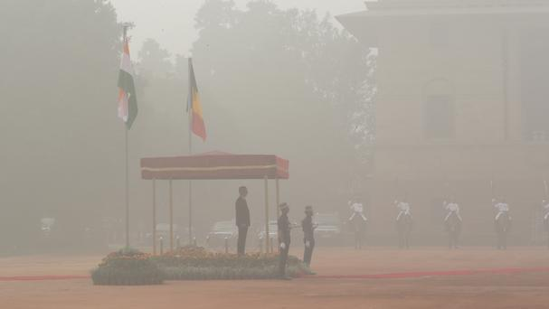 Belgium's King Philippe inspects a military guard of honour in the smog at the presidential palace in New Delhi (AP)
