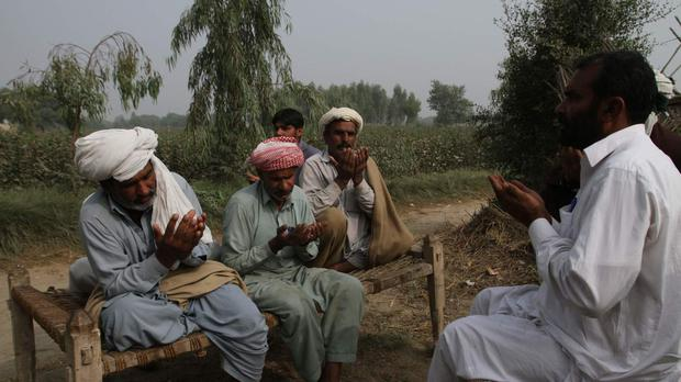 Villagers pray for poisoning victims during a condolence visit to the families in Basti Lashari (AP)