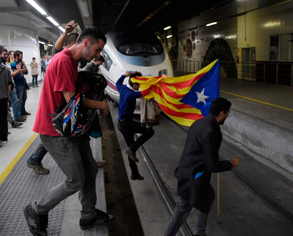 Protesters carrying a pro-independence Catalan Estelada flag jump on tracks at the Sants Station in Barcelona Photo: AFP/Getty