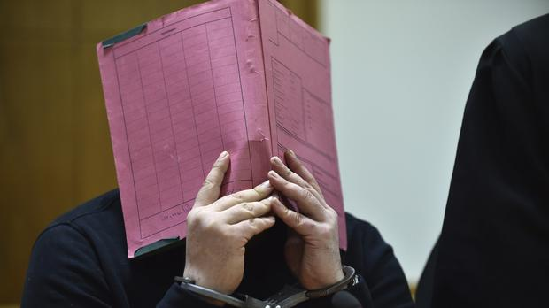 Niels Hoegel covers his face during his trial at the regional court in in Oldenburg (AP)