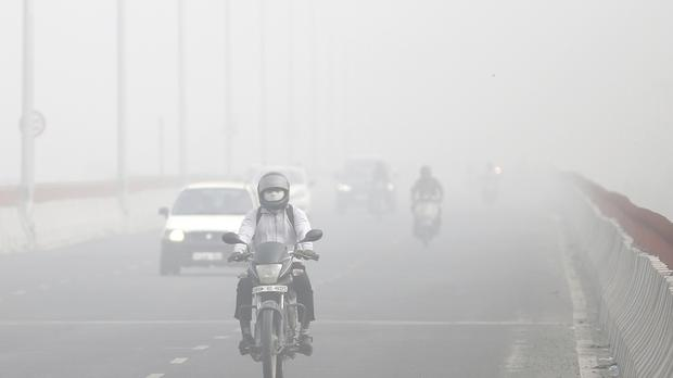 Motorists drive through the smog in New Delhi (AP)