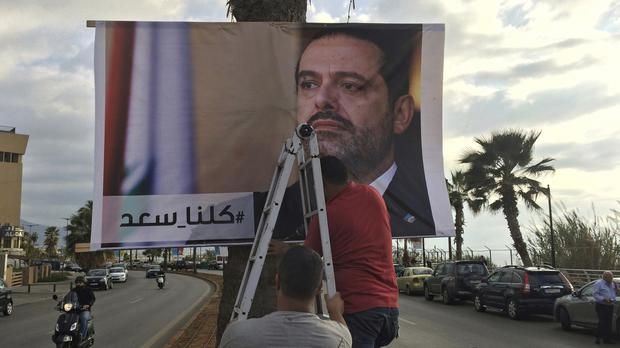 Workers hang a poster of outgoing Prime Minister Saad Hariri with Arabic words that read