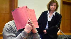 Niels Hoegel hides behind a folder in court.