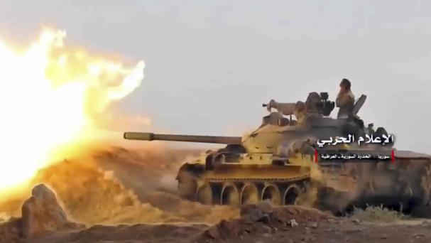 A tank fires on militants' positions on the Iraq-Syria border. (Syrian Central Military Media, via AP)