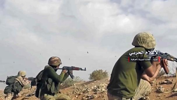 Syrian pro-government troops taking up positions and firing on militants' positions on the Iraq-Syria border (AP)
