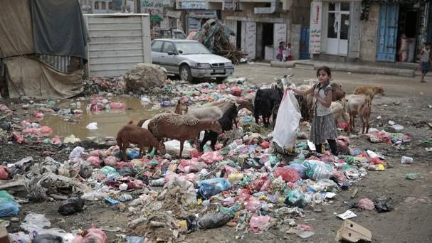 A girl scavenges at a dump in a street in Sanaa, Yemen (AP)