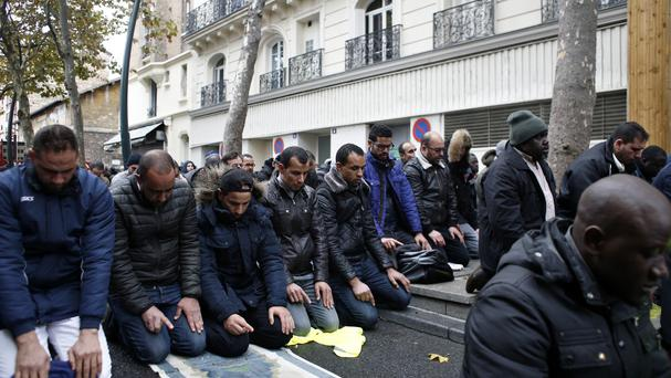 Muslims pray in the street for Friday prayer in the Paris suburb of Clichy la Garenne (AP)