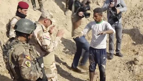 Iraqi security forces speak to shepherd Khalaf Luhaibi about mass graves found in an area recently retaken from the Islamic State group (Kirkuk Governor's Office via AP)