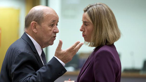 French Foreign Minister Jean-Yves Le Drian speaks with European Union foreign policy chief Federica Mogherini during a meeting of EU foreign and defence ministers in Brussels (AP)