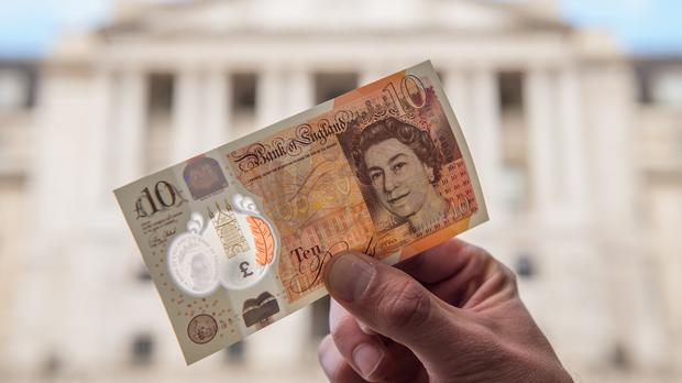 A man holds a new ten pound note featuring Jane Austen outside the Bank of England in London (PA)
