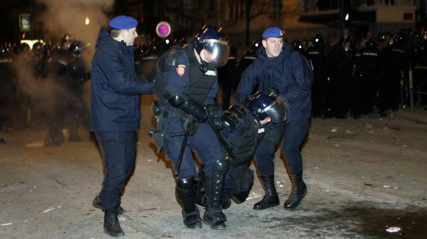 Officers carry an injured policeman away from the US Embassy in Belgrade in 2008 (Darko Vojinovic/AP/PA)