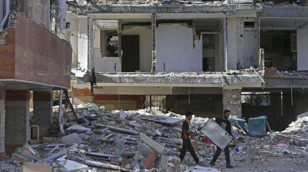 Earthquake survivors carry their belongings in front of damaged buildings in Sarpol-e-Zahab (Vahid Salemi/AP/PA)