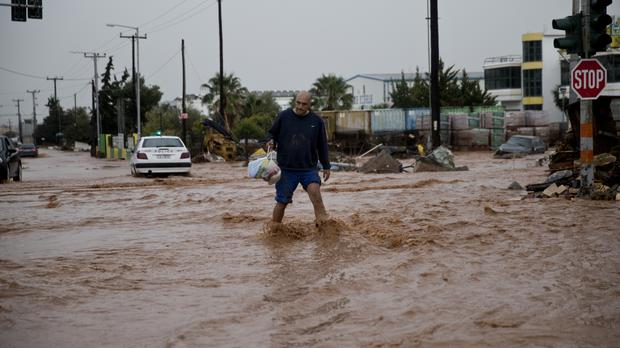 A man walks on a flooded street in the municipality of Mandra in western Athens (Petros Giannakouris/AP/PA)