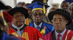 Robert Mugabe, centre, arrives to preside over a student graduation ceremony at Zimbabwe Open University on the outskirts of Harare (AP)