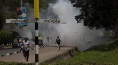 People run for safety on the main Uhuru Highway as police fire tear gas (AP)
