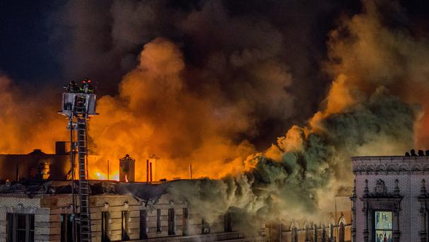 Firefighters battle a large fire on the top floors of an apartment building in New York City's Harlem neighbourhood (AP)
