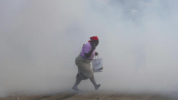 A woman is caught in tear gas during running battles with police in Kibera Slums in Nairobi, Kenya (AP/Brian Inganga)