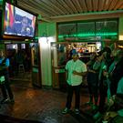 Disappointed Zimbabweans at a bar in downtown Harare watch a televised address to the nation by President Robert Mugabe Photo: AP