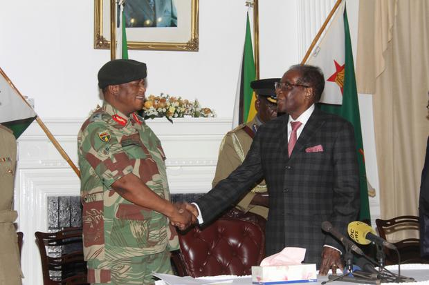 Zimbabwean President Robert Mugabe, right, shakes hands with Army General Constantino Chiwenga before delivering his speech at State House in Harare last night. Photo: AP