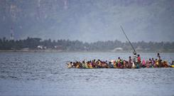 Rohingya Muslims aboard a makeshift raft as they cross from Burma into Bangladesh (AP)