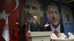 Backdropped by posters of Turkey's founding father Mustafa Kemal Ataturk, left, and himself, Turkey's President Recep Tayyip Erdogan addresses provincial leaders (AP)
