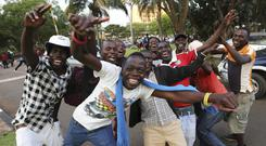 Zimbabweans celebrate the resignation in the streets of Harare (Tsvangirayi Mukwazhi/AP)