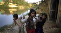 Rohingya Muslim girls carry water pots in Kutupalong refugee camp in Bangladesh (AP)
