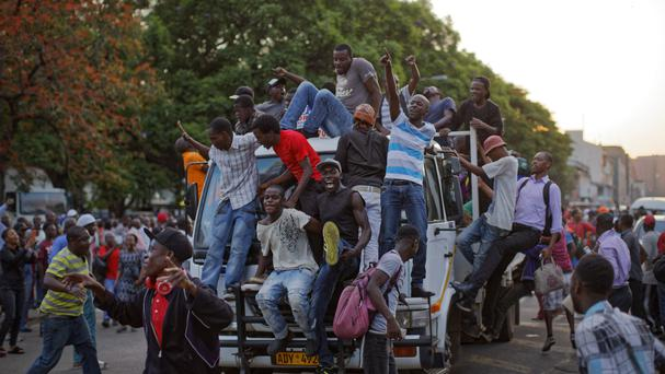 Zimbabweans celebrate outside the parliament building after hearing Robert Mugabe had resigned (AP)