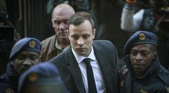 File photo of Oscar Pistorius, centre, arriving at the High Court in Pretoria, South Africa, in 2016 (AP)