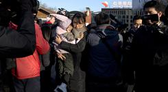 A woman leaves with a child after saying she came to withdraw the child from the RYB kindergarten in Beijing (AP/Ng Han Guan)