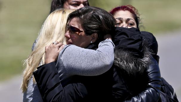 Distressed relatives of a missing submarine crew member comfort each other (AP)