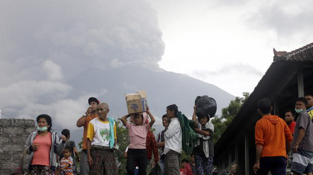 Villagers carry their belongings during an evacuation following the eruption of Mount Agung (AP Photo/Firdia Lisnawati)