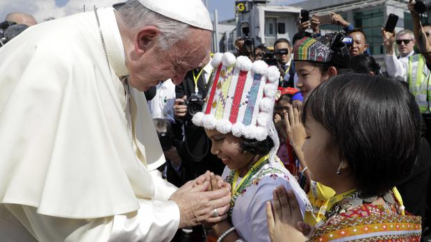 Pope Francis is greeted by young children in traditional clothes on his arrival at Yangon airport (AP)