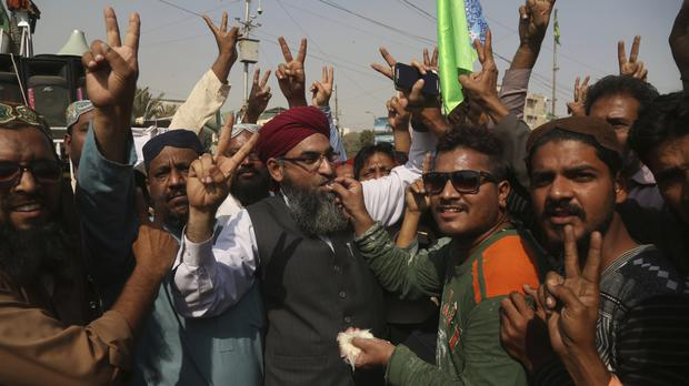 Protesters celebrate after the resignation of Pakistan's law minister (AP)