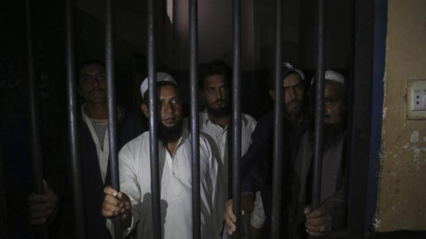 Relatives of a newlywed couple stand behind bars at a police station in Karachi (AP)