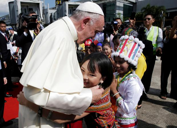 A young girl embraces Pope Francis as he arrives at Yangon International Airport in Myanmar yesterday. Photo: Reuters/Max Rossi