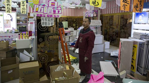 Bi Yan'ao stands in a cosmetics shop he is helping to clear out after eviction orders were handed down in Beijing (Ng Han Guan/AP)