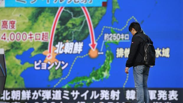 A man stands in front of a huge screen showing a TV news programme reporting North Korea's missile launch, in Tokyo (Shizuo Kambayashi/AP/PA)