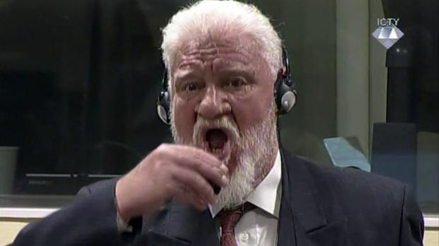 Slobodan Praljak brings a bottle to his lips during a Yugoslav war crimes tribunal in The Hague (ICTY/AP/PA)