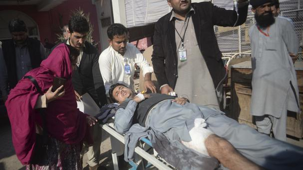 Staff rush an injured man to a hospital after militants stormed the agriculture institute in Peshawar, Pakistan (AP Photo/Muhammad Sajjad)