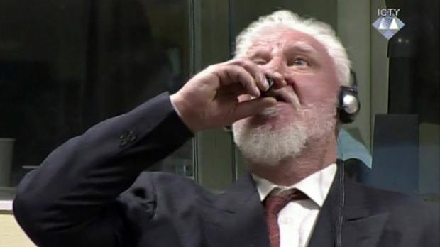 Slobodan Praljak puts the bottle to his lips during the hearing in The Hague (ICTY/AP)