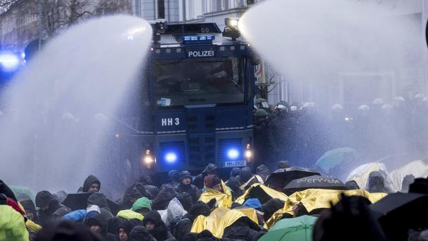 Police use a water cannon to clear a street that is blocked by demonstrators (AP)