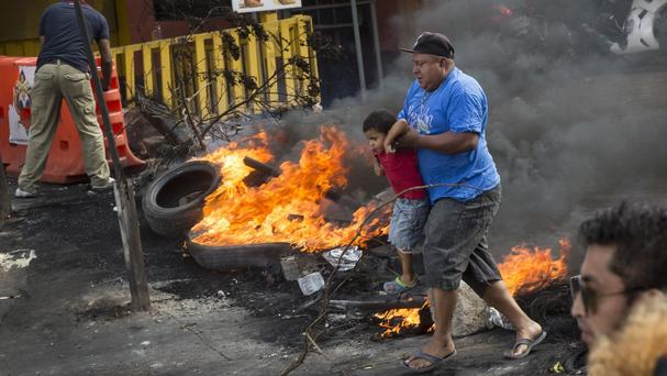 A man carries a boy as they cross a burning barricade erected by supporters of presidential candidate Salvador Nasralla in Honduras (AP Photo/Rodrigo Abd)