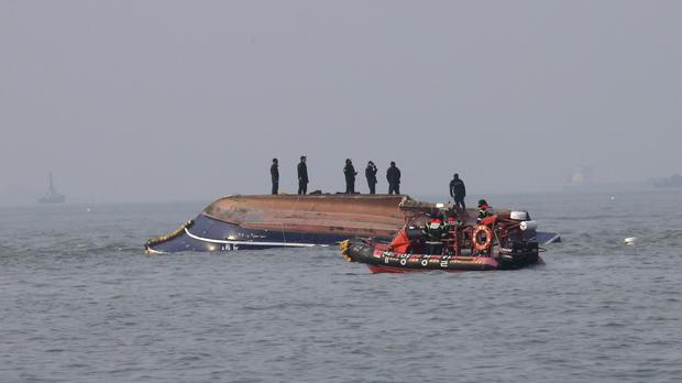 South Korean Coast Guard officers go to the rescue of a capsized fishing boat