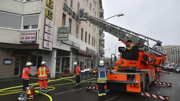 Firefighters after a blaze resulting in deaths and injuries broke out in a building in Saarbruecken, western Germany (AP)