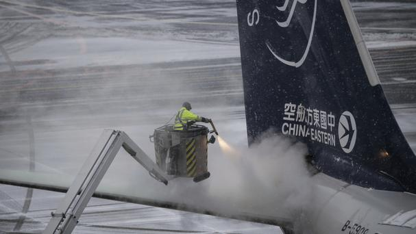 An airport worker defrosts a Chinese plane in Frankfurt (Andreas Arnold/dpa via AP)