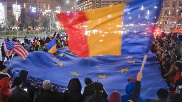 People hold an EU flag during a protest in Bucharest (AP/Vadim Ghirda)